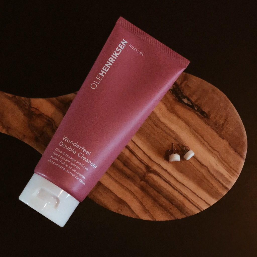 ole henriksen wonderfeel double cleanser flatlay with marble earrings and wood background