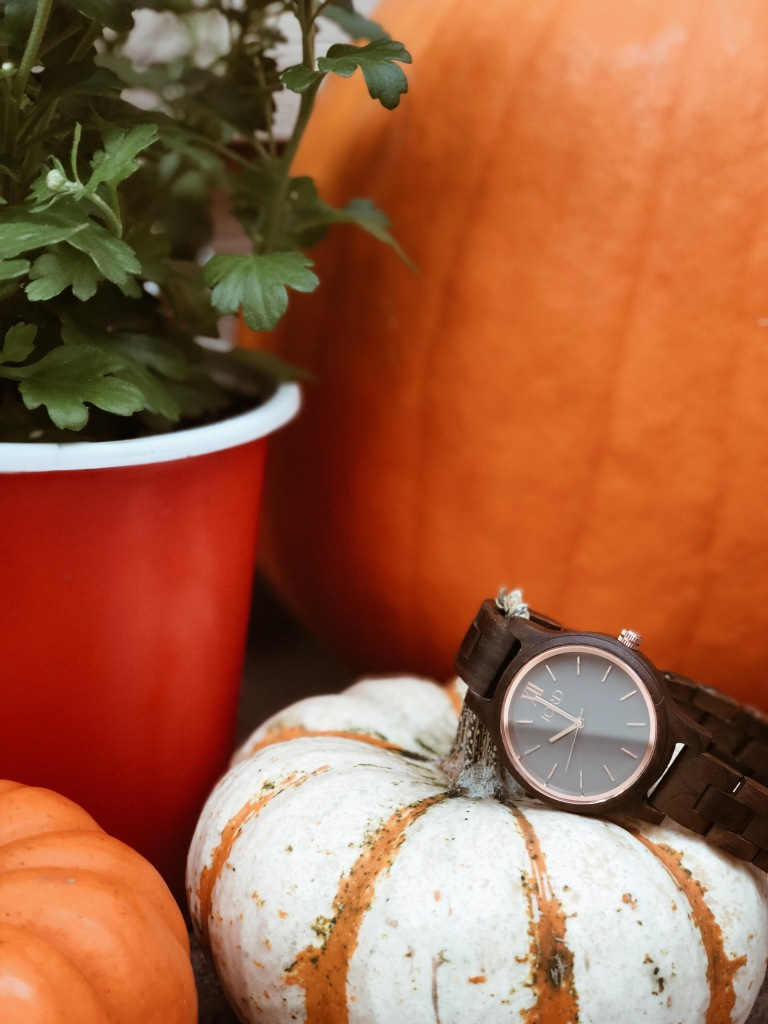 pumpkins and mums with jord wood watch hanging over pumpkin